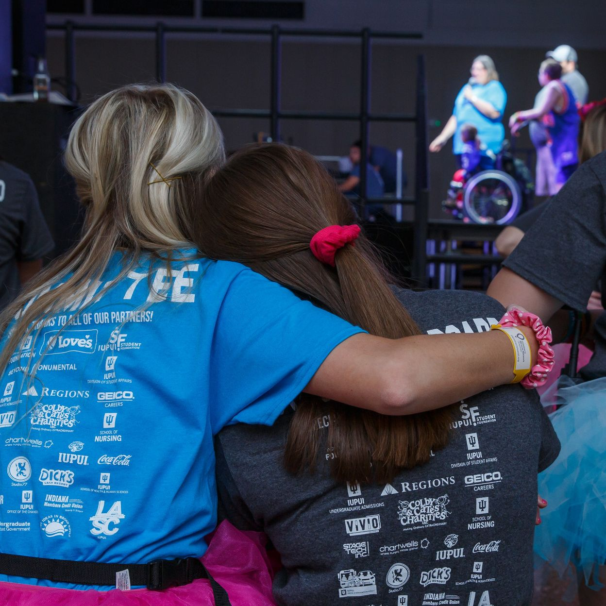 Two IUPUI students hug while watching the programming on the Jagathon stage