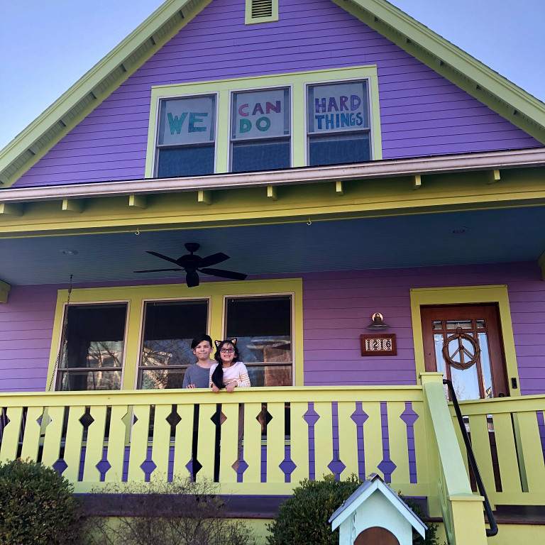 Two children stand on porch of purple house; signs of encouragement hang in windows.