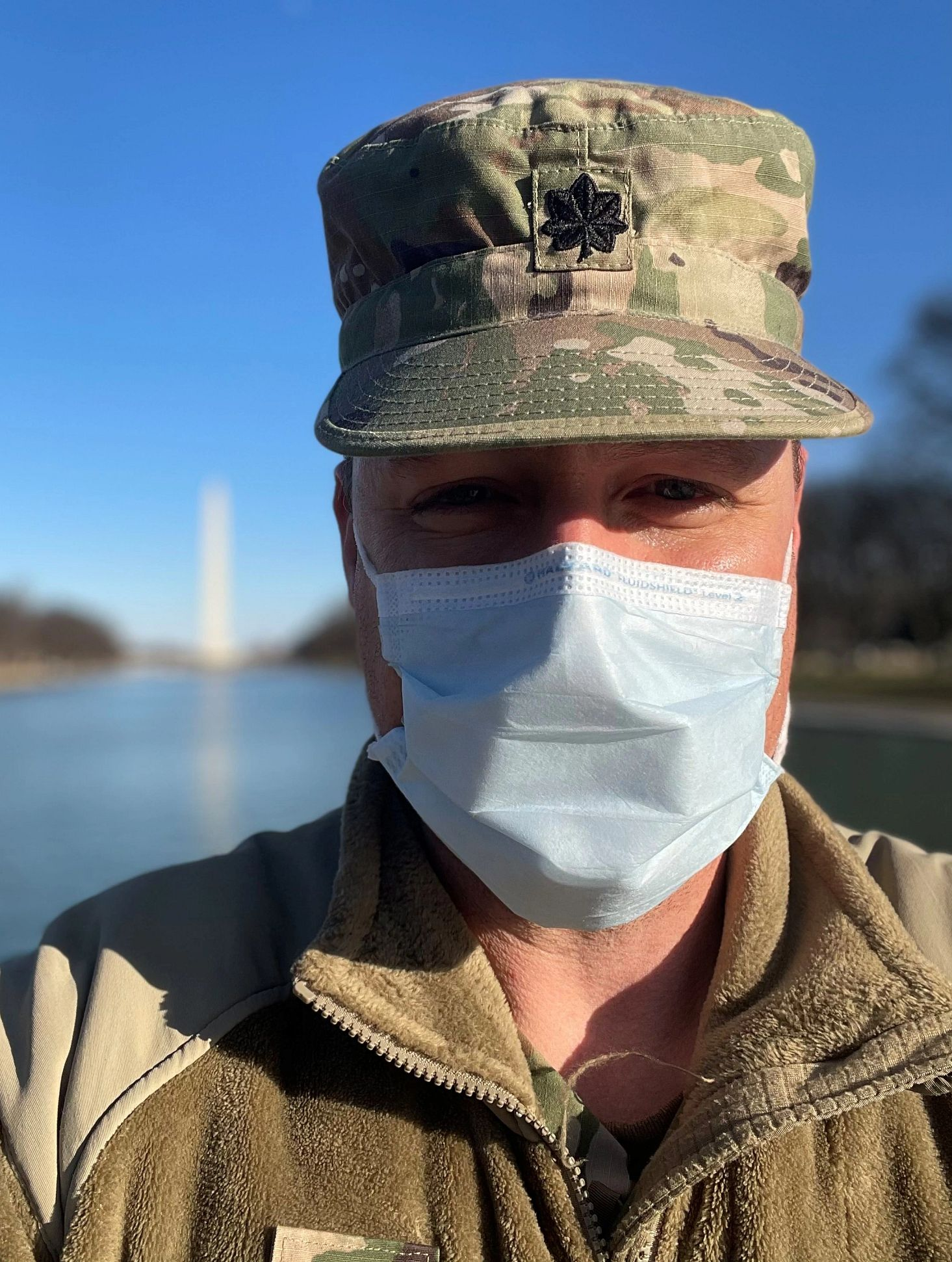 Dr. Sample wears a mask with the Washington Monument behind him