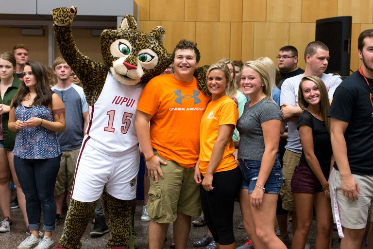 Jazzy the jaguar mascot poses with a group of students