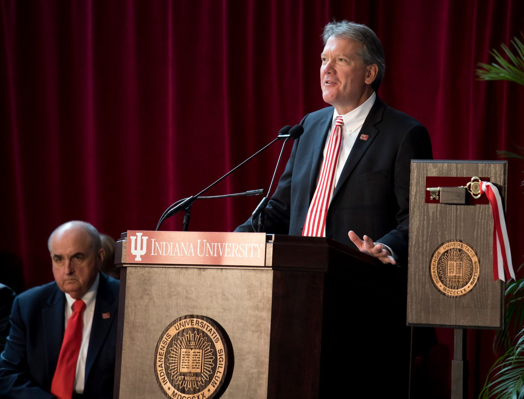 A man gives a speech at a lectern, while a seated man listens