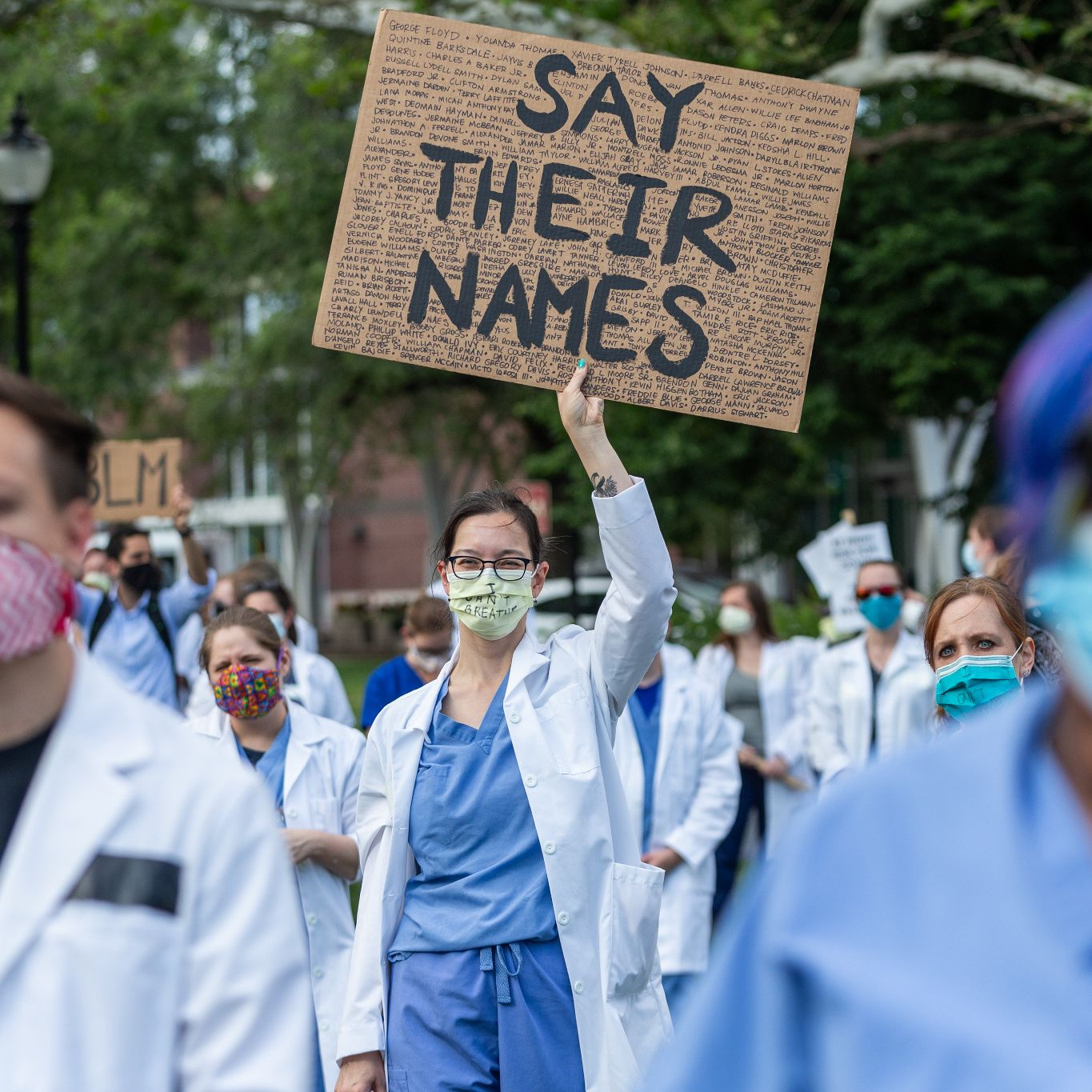 A woman wearing a white coat and mask is holding a sign that says 'say their names'