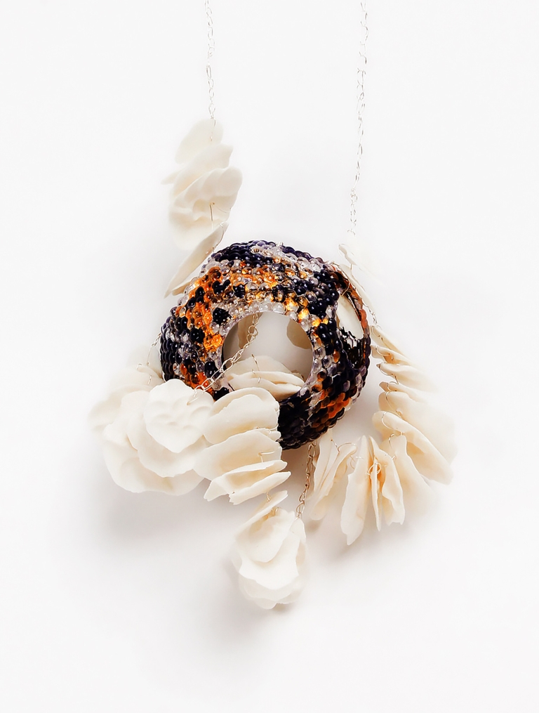 jewelry made by Yingqi 'Puffy' Zhao, a red-amber amulet on a white chain