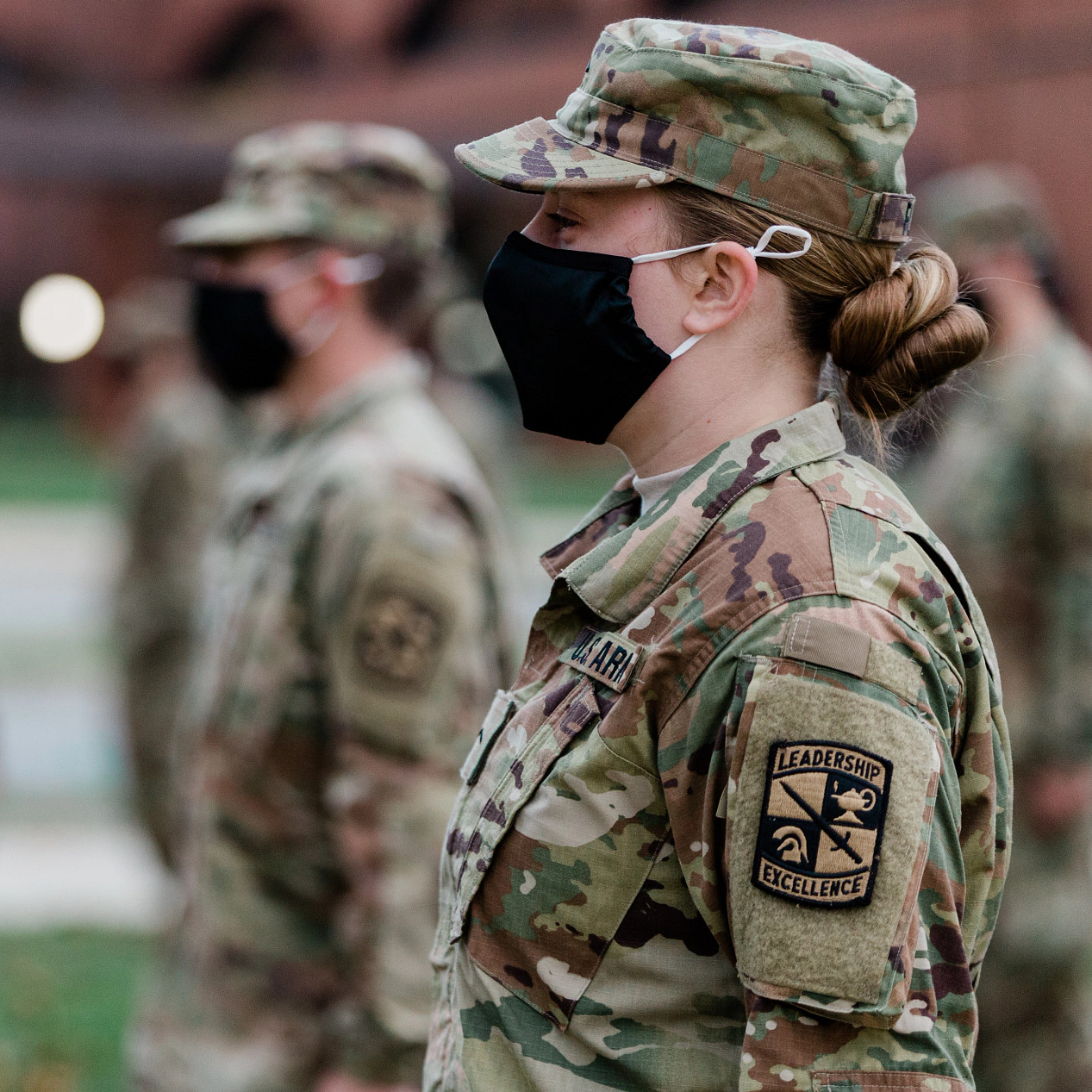 a masked female soldier stands in formation during a ceremony