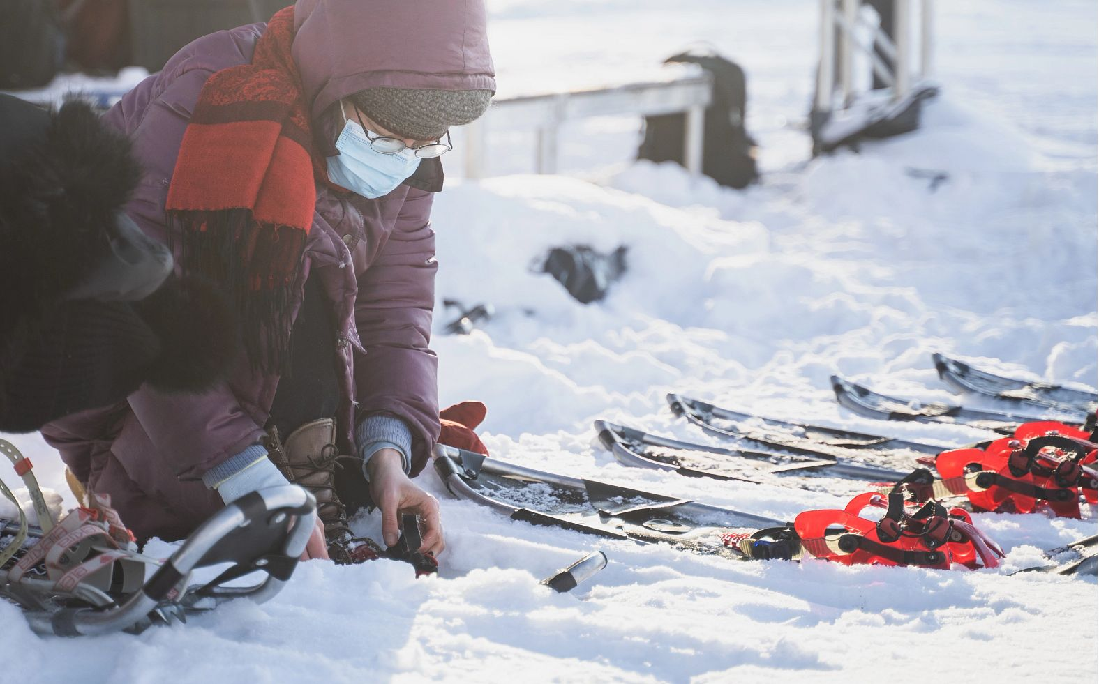 A person puts on a snowshoe