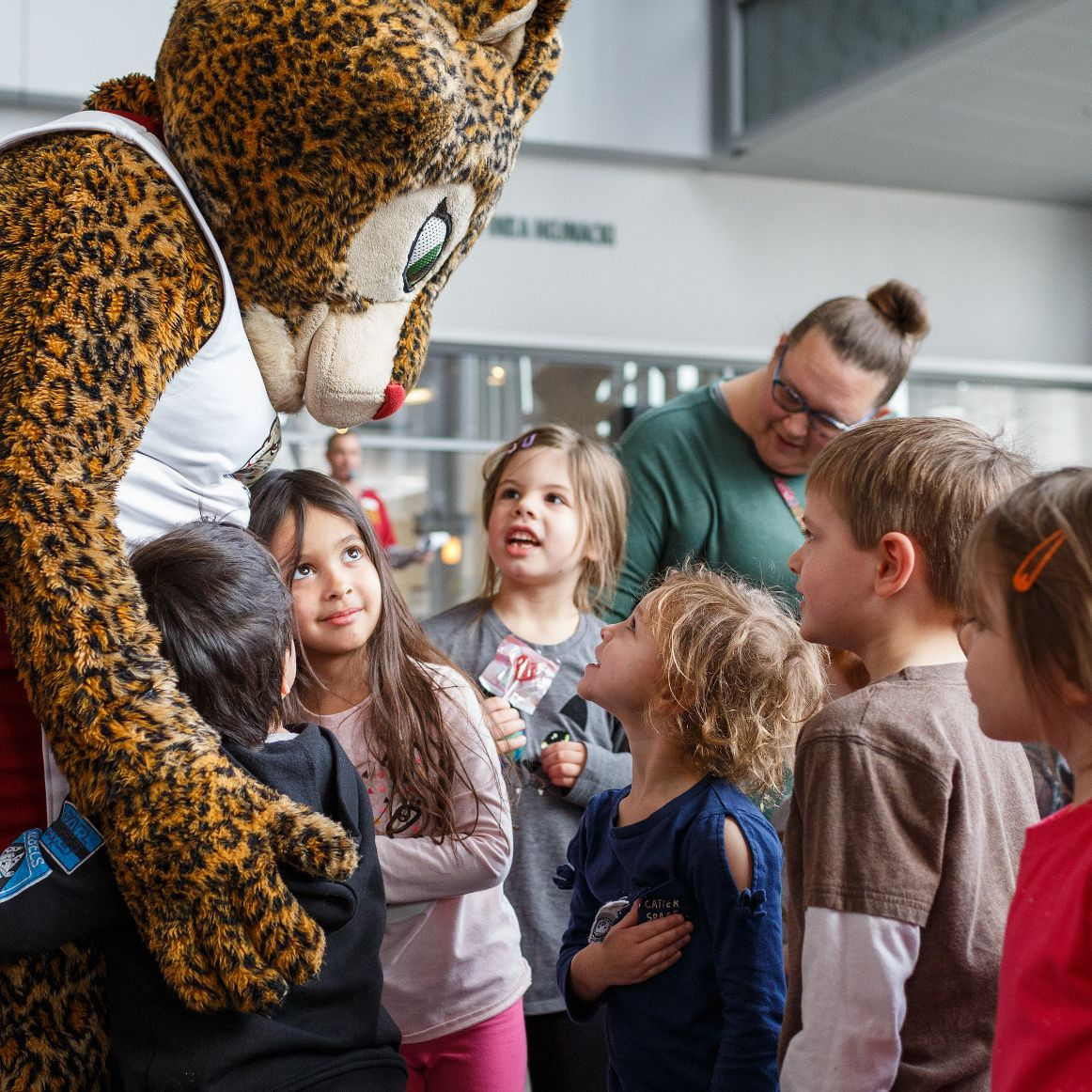 Jazzy the Jaguar mascot hugs kids at the 2020 IUPUI International Festival.