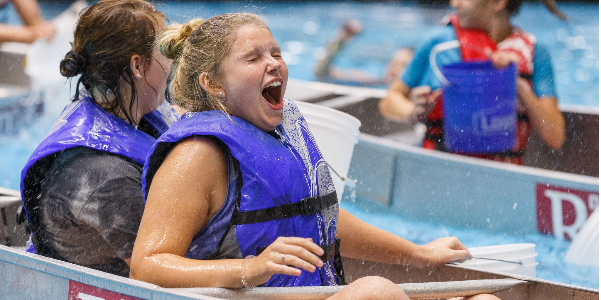 A student reacts to being splashed in a canoe.