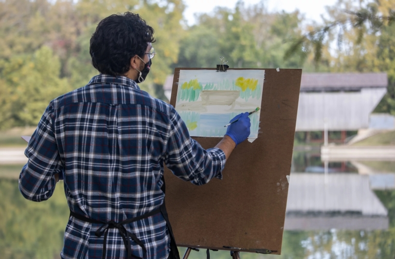 A student paints a covered bridge at Mill Race Park