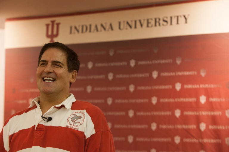 Mark Cuban stands in front of an IU backdrop wearing an IU rugby shirt