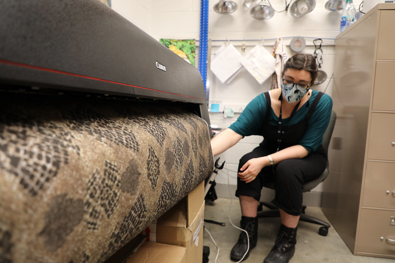 A woman sits next to a digital printer as it prints a strip of fabric with a python pattern