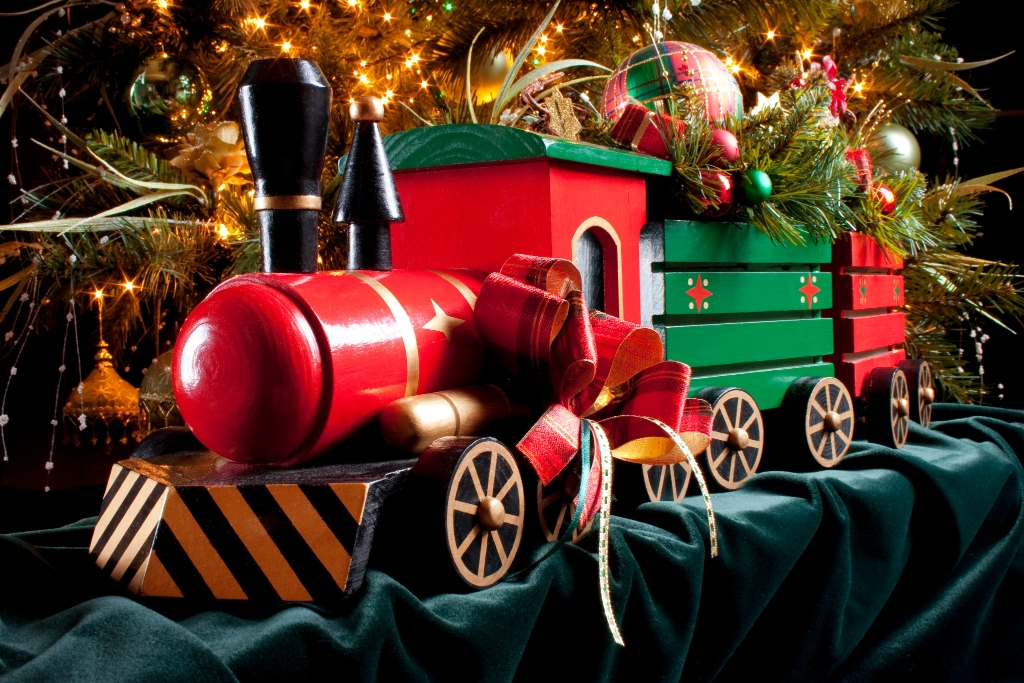 Red-and-green model train decorated for Christmas in front of a tree.