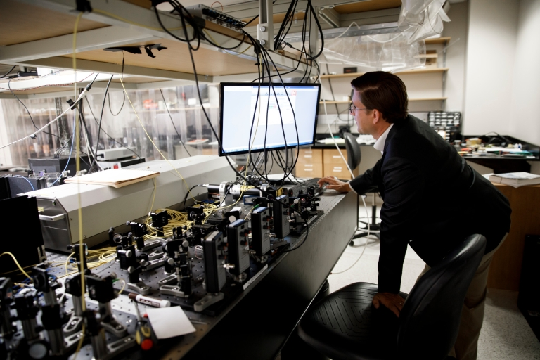Indiana University professor Phil Richerme works with laser equipment in a lab.