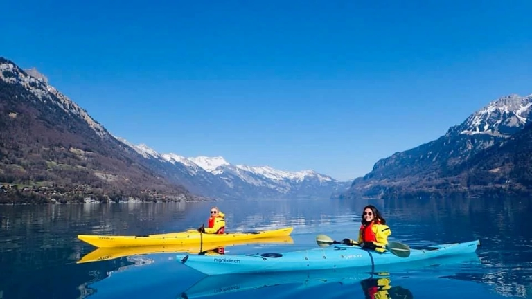Two students in kayaks on a lake in Switzerland.