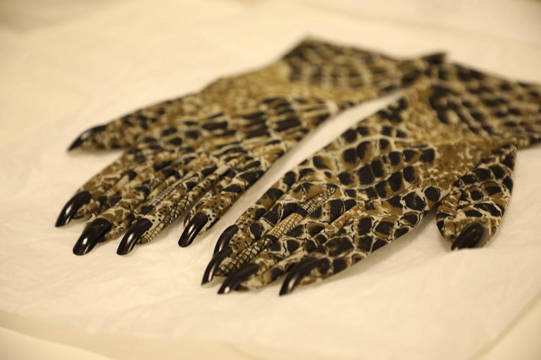A pair of python-patterned gloves with black fingernails