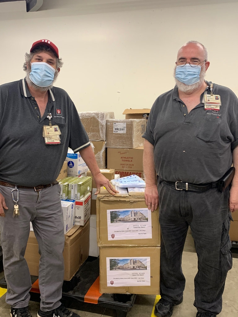 IU Health employees wearing masks and standing next to boxes of donated masks