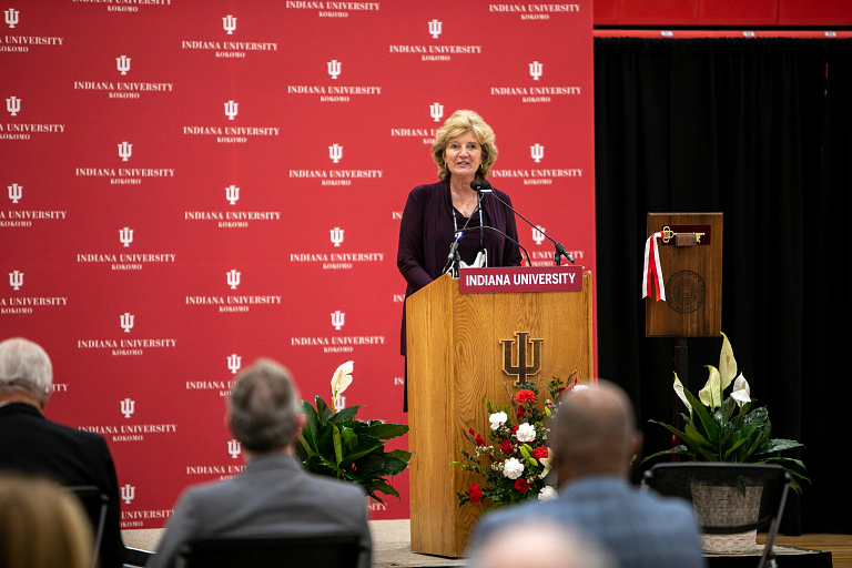 Susan Sciame-Giesecke speaks from a IU podium in front of an IU backdrop