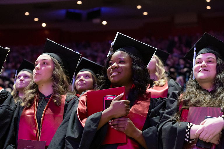 Students wearing caps and gowns hold their degrees during a commencement ceremony