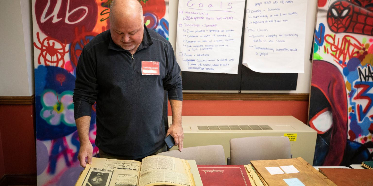 A man looks at a Union Board scrap book