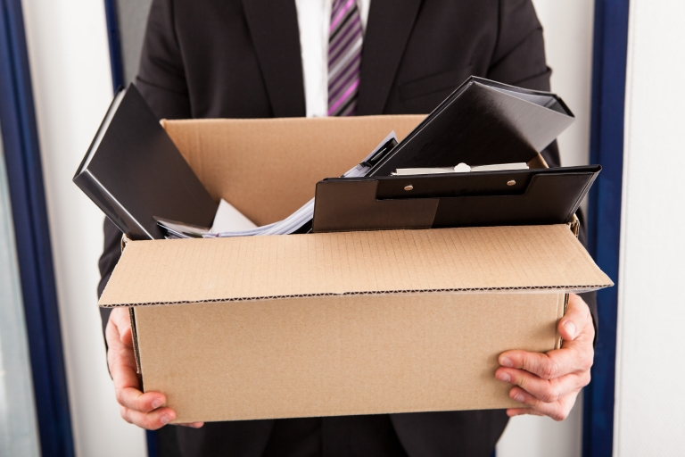 Man in suit holding a box of office supplies