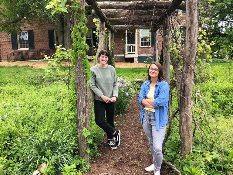 Two women stand in garden