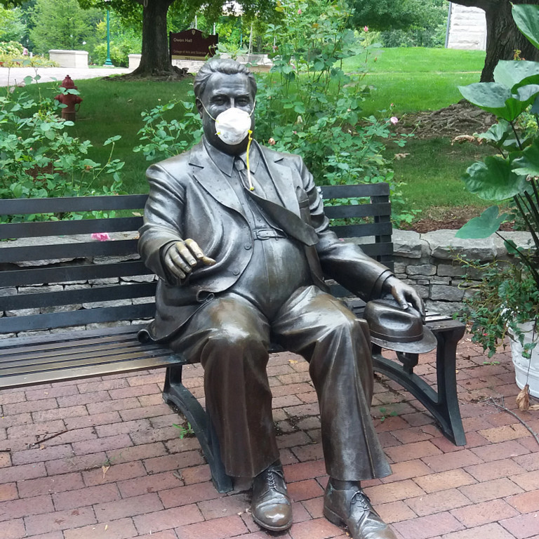 Herman B Wells statue with a COVID-19 mask