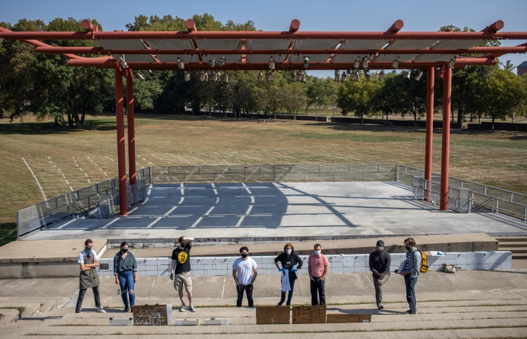 A class looks at paintings set up at a park amphitheater