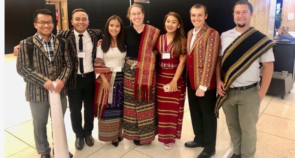 Assistant professor Berkson poses with a group dressed in Burmese garb.