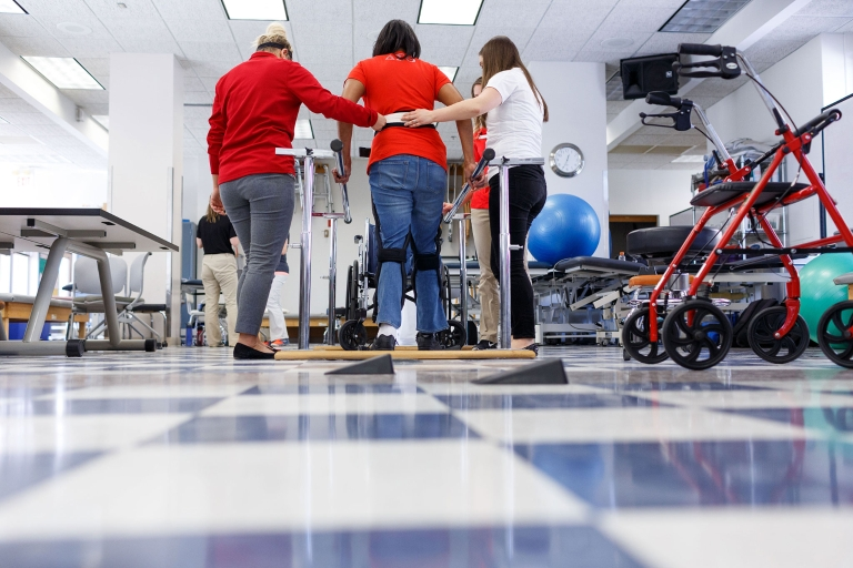 A patient receives assistance walking during a physical therapy session