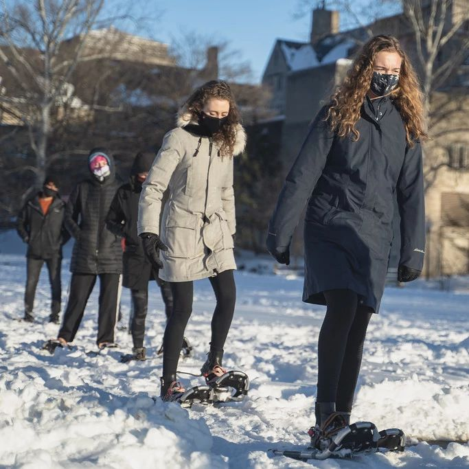 A group of people practice snowshoeing