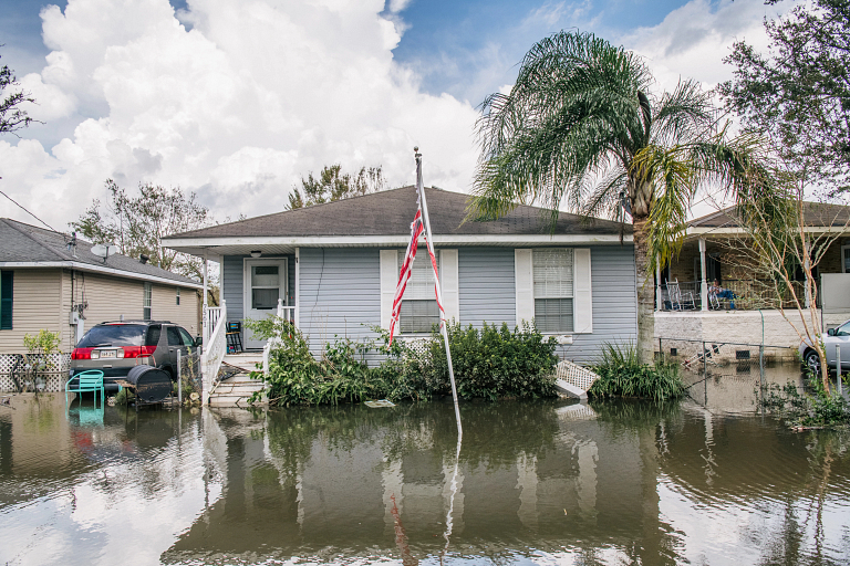 Floodwaters surround houses and a car