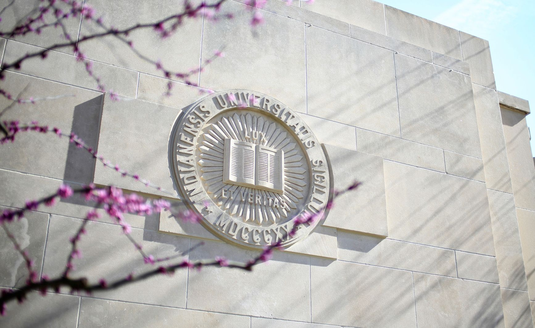 The Indiana University seal is seen carved into a limestone building behind tree blossoms