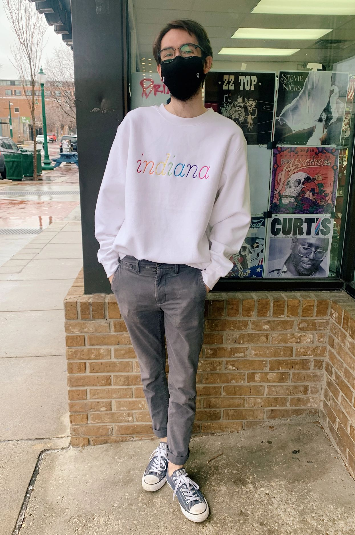 """Student stands outside Tracks wearing a white sweatshirt with a rainbow """"Indiana"""" embroidered on it"""