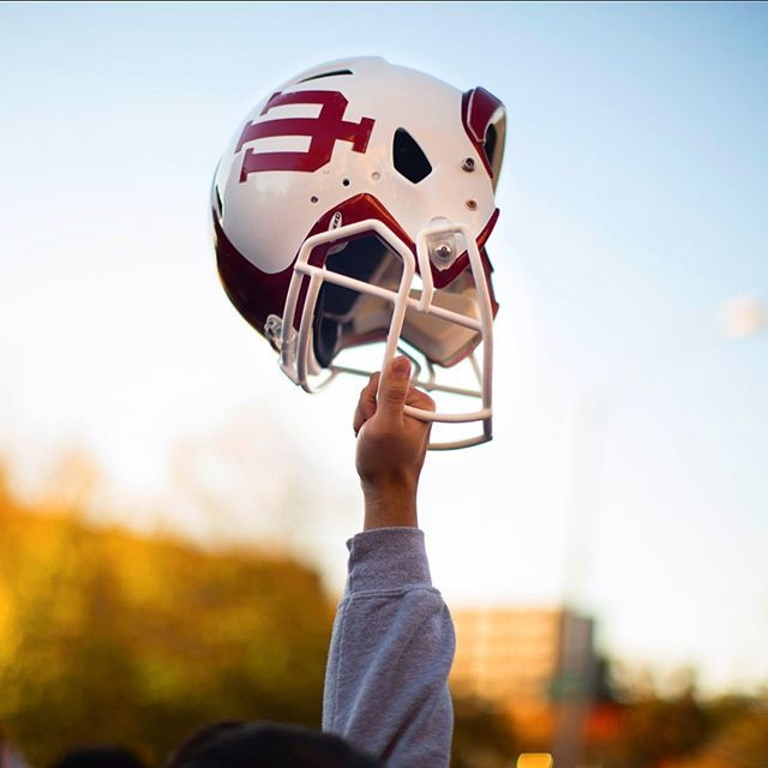 A hand holds up a football helmet