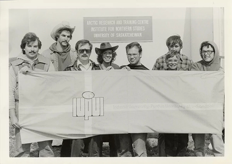 eight people standing in a black and white photo behind a flag with IUPUI on it