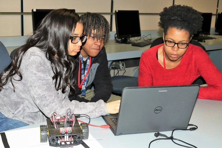 iDEW students look at a laptop with a robotic car on the table next to it
