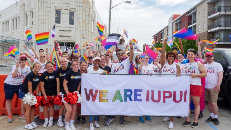 """A large group of people hold pride flags and a banner that reads """"We are IUPUI"""""""