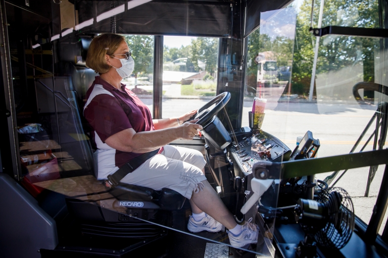 A bus driver wearing a mask seated behind a plexiglass shield