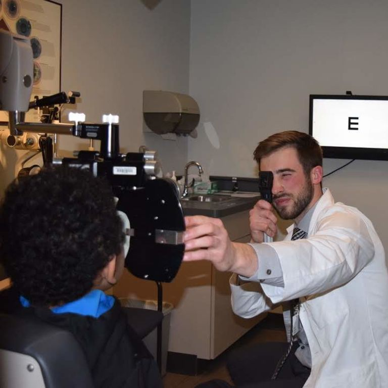 An IU optometry student provides a free eye exam to a person in need