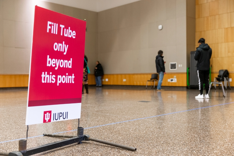 "a sign that says ""fill tube only beyond this point"" with people in the background"
