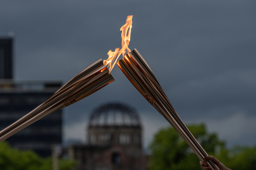 Two Olympic torches passing the flame