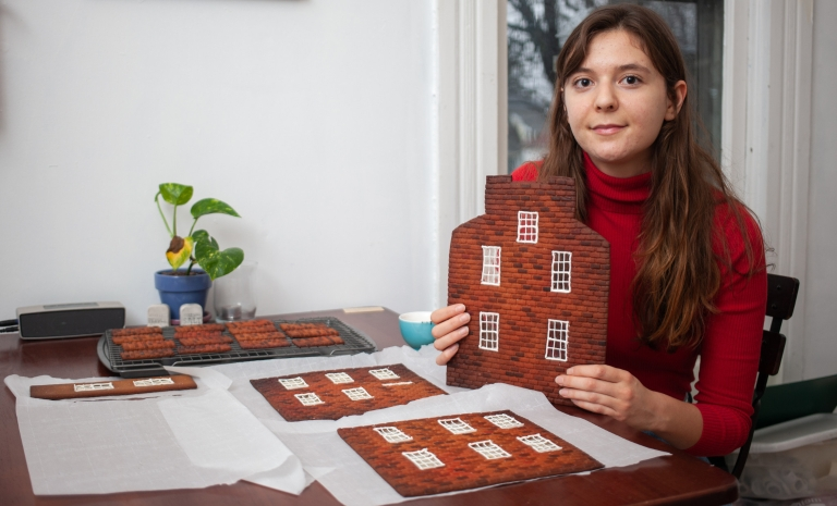 Mary Figueroa works on a gingerbread house